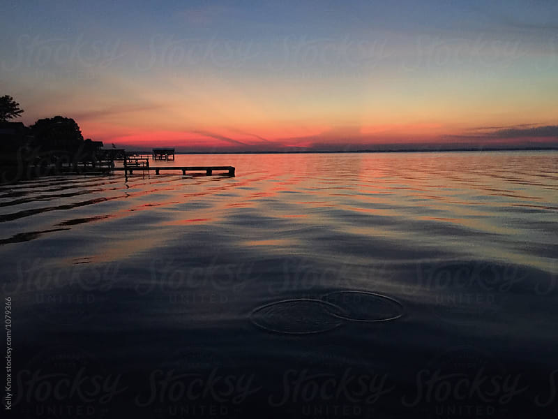 sunset over a lake by Kelly Knox for Stocksy United