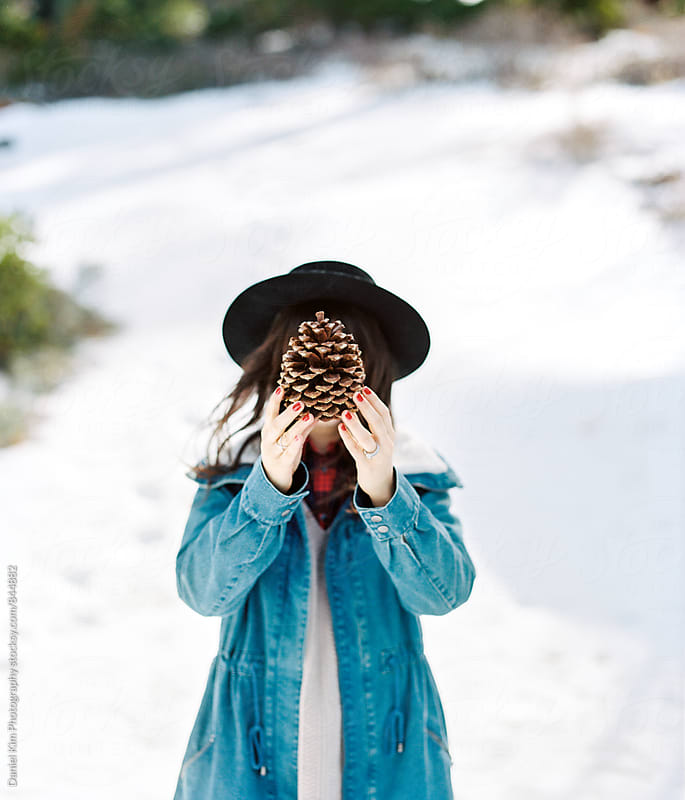 Young woman holding pinecone over face by Daniel Kim Photography for Stocksy United