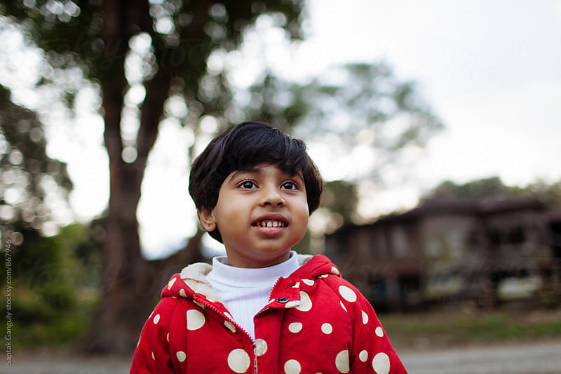 Outdoor portrait of a child smiling by Saptak Ganguly for Stocksy United