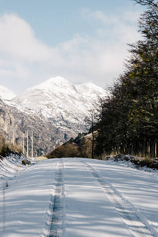 Snow covered road with tire tracks by Justin Mullet for Stocksy United