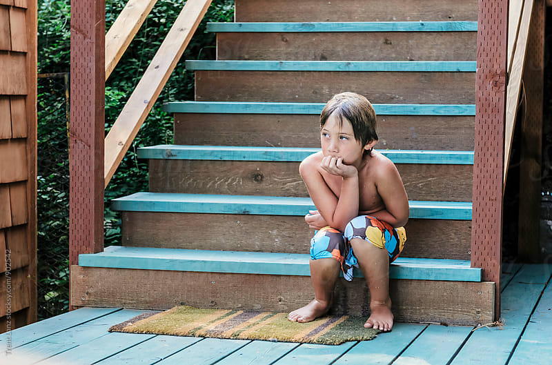 Lonely boy sitting on steps pouting by Trent Lanz for Stocksy United