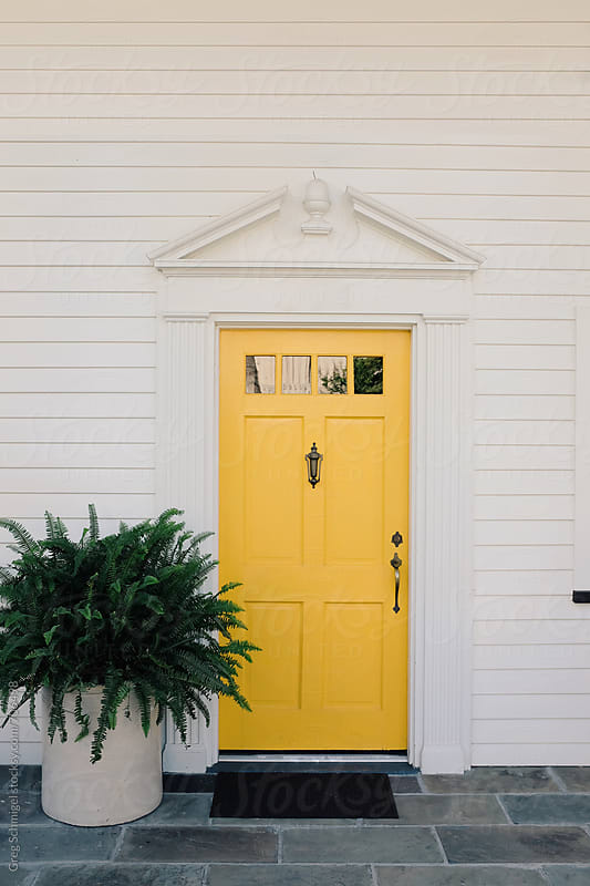 A white house with a bright yellow door and a large green fern plant by Greg Schmigel for Stocksy United
