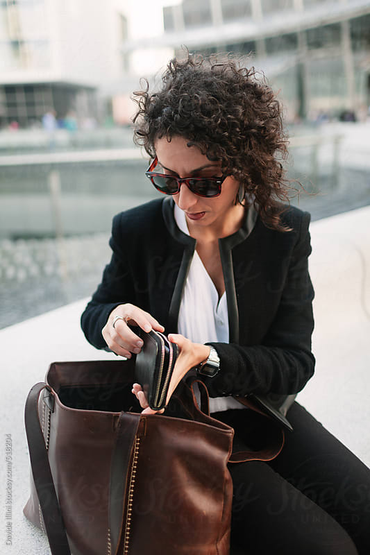 Businesswoman looking into wallet by Davide Illini for Stocksy United