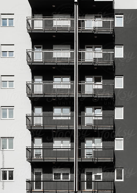 Grey and white building with balcony by Marko Milanovic for Stocksy United