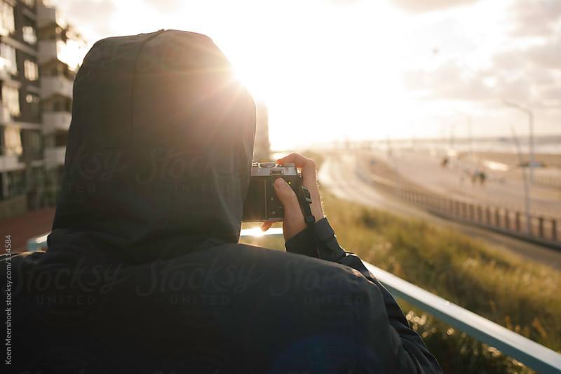 Hooded man takes a picture of a boulevard by Koen Meershoek for Stocksy United