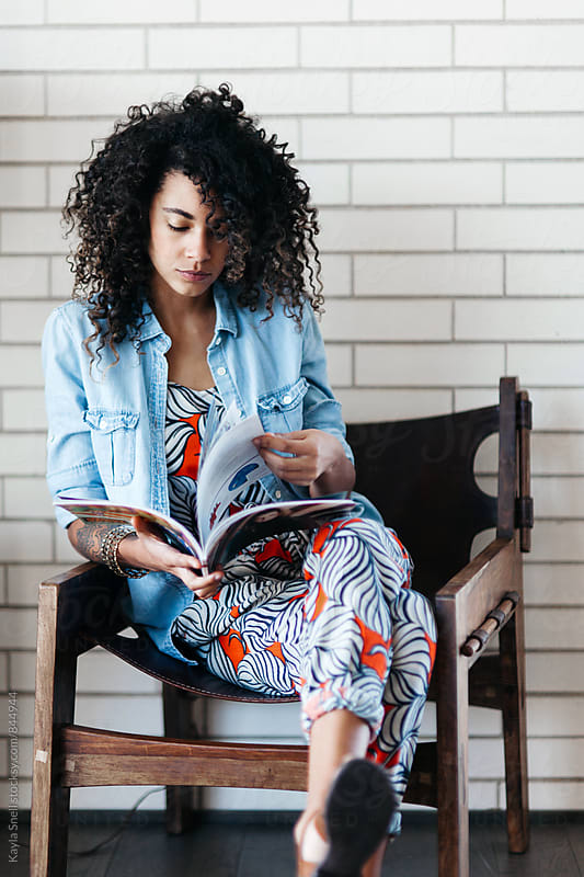 Young woman reading a magazine by Kayla Snell for Stocksy United