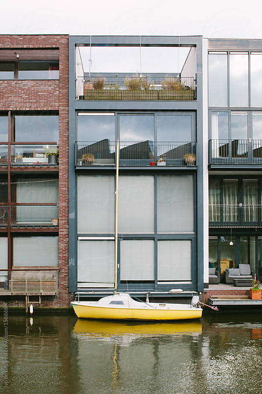 Yellow sailing boat docked at the back of a modern canal house by Ivo de Bruijn for Stocksy United