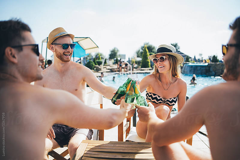 Friends Making a Toast by the Swimming Pool by Lumina for Stocksy United