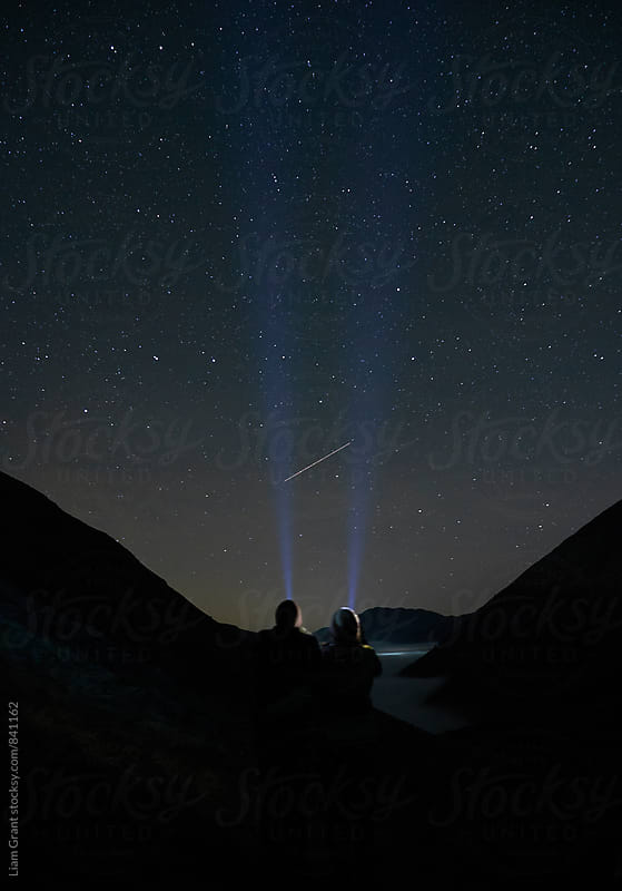 Young couple watching shooting stars in the mountains. Cumbria, UK. by Liam Grant for Stocksy United