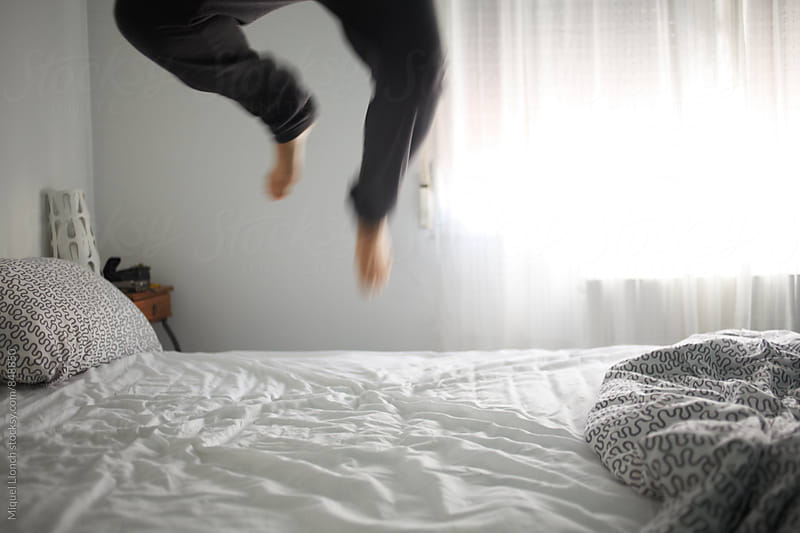 Vigorous wake up with a jump on the bed by Miquel Llonch for Stocksy United