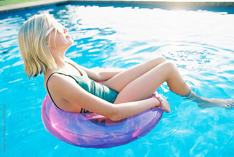 teen girl sitting in pink floaty in swimming pool by wendy laurel for Stocksy United