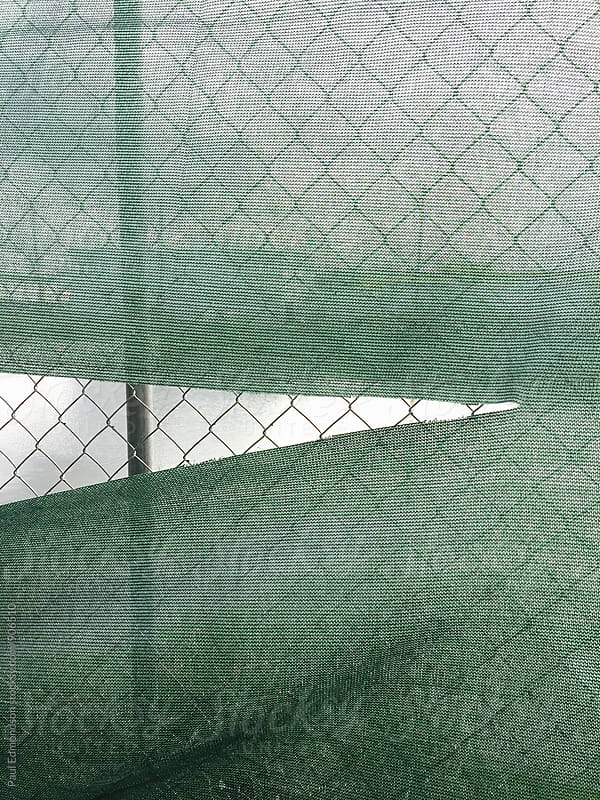 Torn green fabric covering chain-link fence by Paul Edmondson for Stocksy United