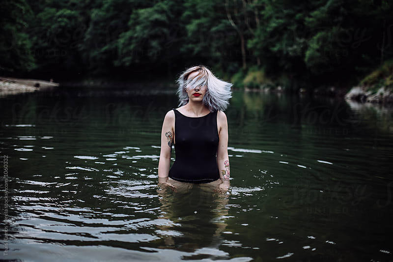 woman shaking her head in the river by Thais Ramos Varela for Stocksy United