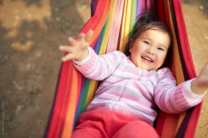 one happy little asian girl lying in hammock by Bo Bo for Stocksy United