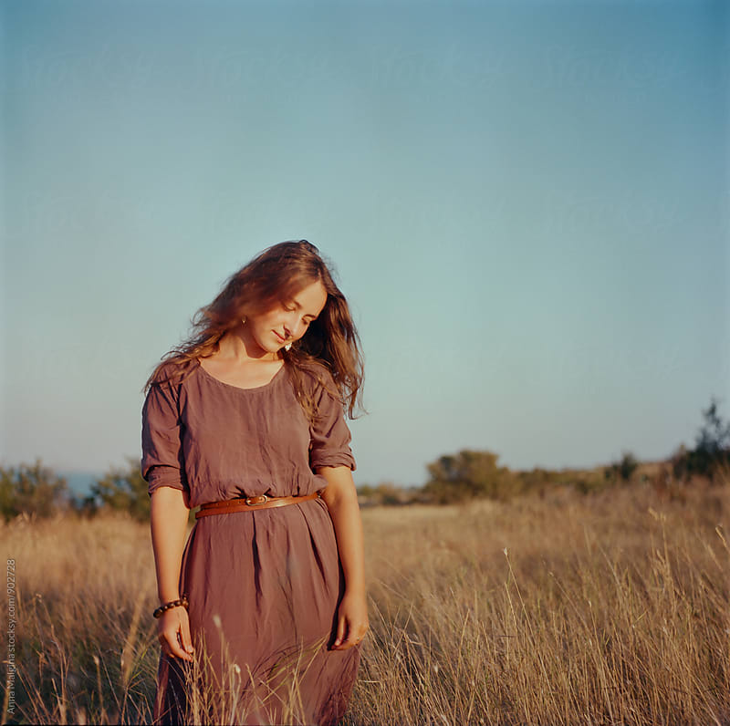 A film portrait of young beautiful woman in the grass during sunset by Anna Malgina for Stocksy United