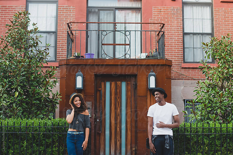 Happy couple standing in front of apartment building in the city by Lauren Naefe for Stocksy United