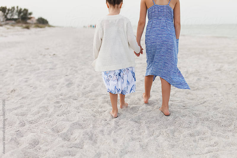 Sisters walking along beach holding hands by Amanda Worrall for Stocksy United