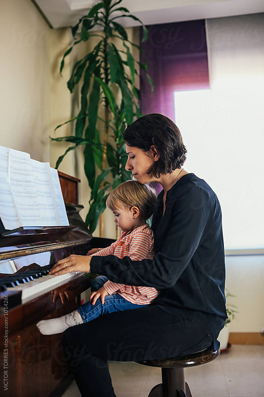 Mother Playing Piano at Home with Her Adorable Little Girl by VICTOR TORRES for Stocksy United