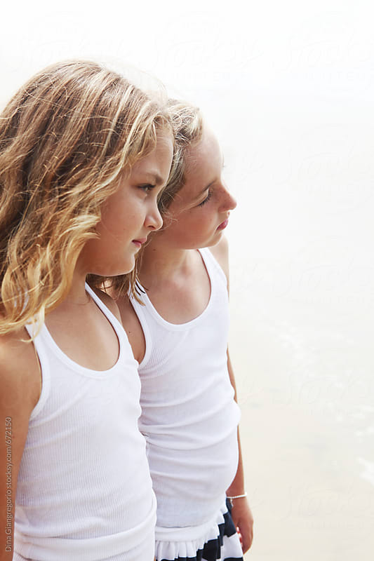 Two Young Girls Looking off Into The Distance by Dina Giangregorio for Stocksy United