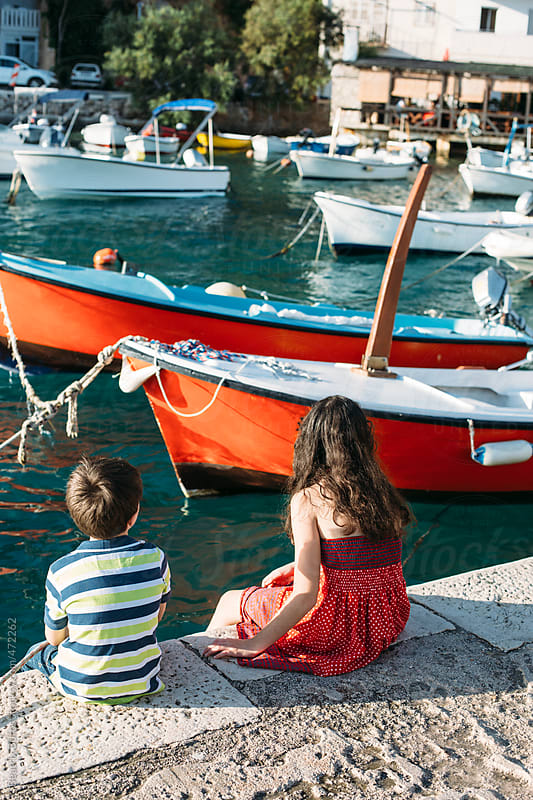 Boy and girl looking at the different boats by the sea by Beatrix Boros for Stocksy United