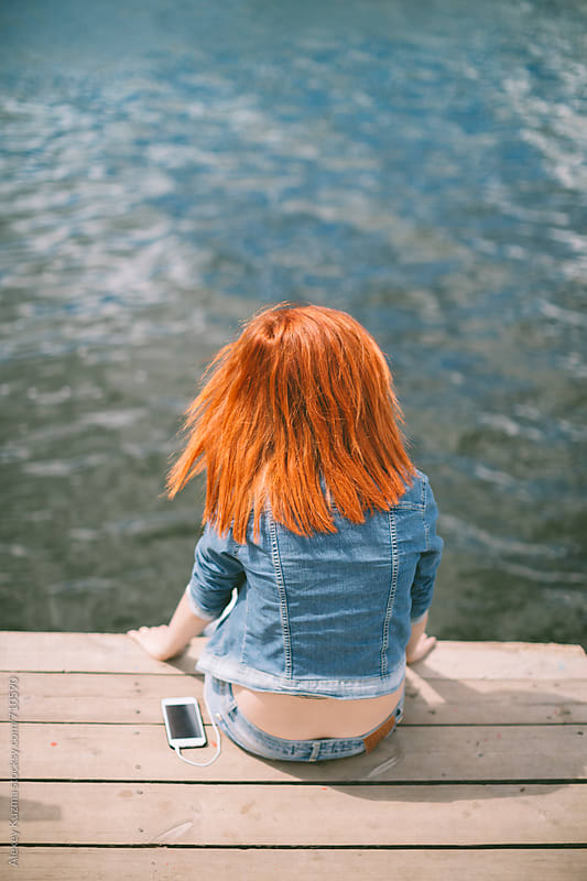 red hair young girl  sitting on a dock from behind by Alexey Kuzma for Stocksy United