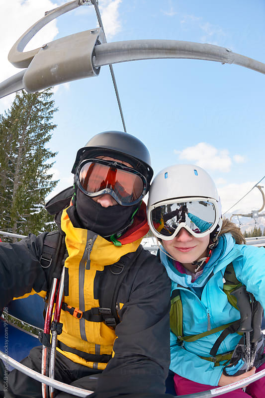 Couple going up the mountain by ski lift by RG&B Images for Stocksy United