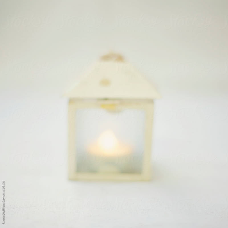 Blurred image of a vintage lamp with burning candle in it by Laura Stolfi for Stocksy United