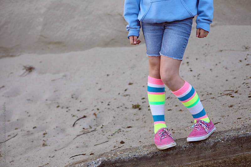 Little girl in cut off jeans, striped knee highs and pink sneakers by Carolyn Lagattuta for Stocksy United