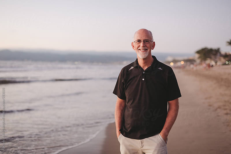 Content middle aged, retired man smiling outside on ocean beach at sunset by Rob and Julia Campbell for Stocksy United