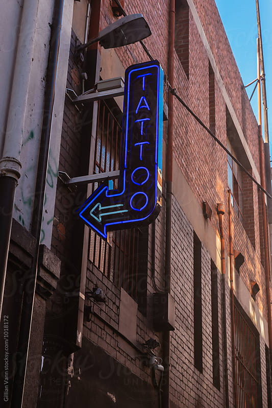 neon tattoo sign with arrow by Gillian Vann for Stocksy United