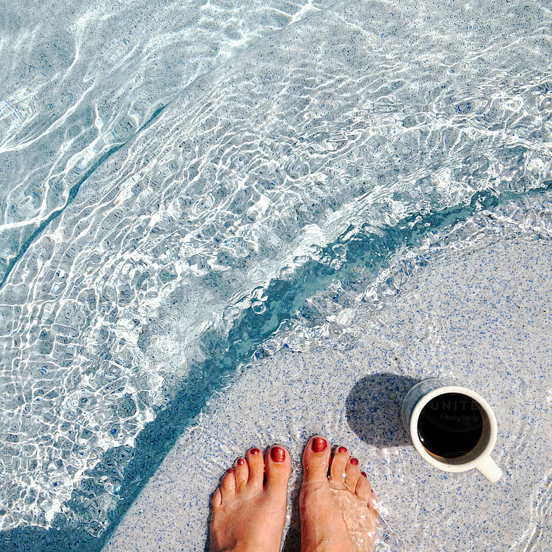 Women's feet with a coffee cup at the pool by Holly Clark for Stocksy United