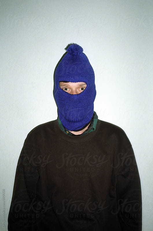 Young man in balaclava on light background by Dina Lun for Stocksy United