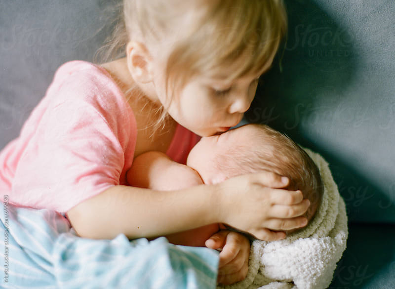 Little girl kissing her baby brother by Marta Locklear for Stocksy United
