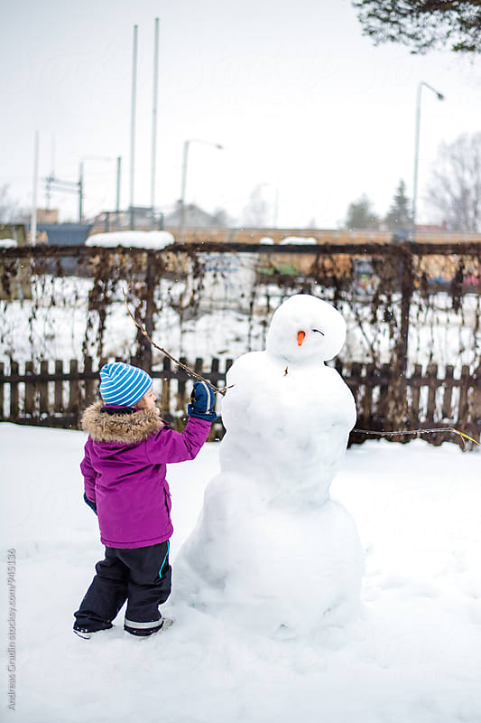 girl and snowman by Andreas Gradin for Stocksy United