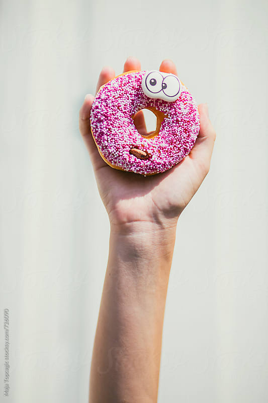 Female hand holding a pink donut with eyes by Maja Topcagic for Stocksy United