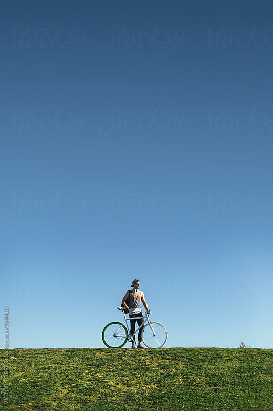 Youn Man Walking Uphill with His Bicycle by VICTOR TORRES for Stocksy United