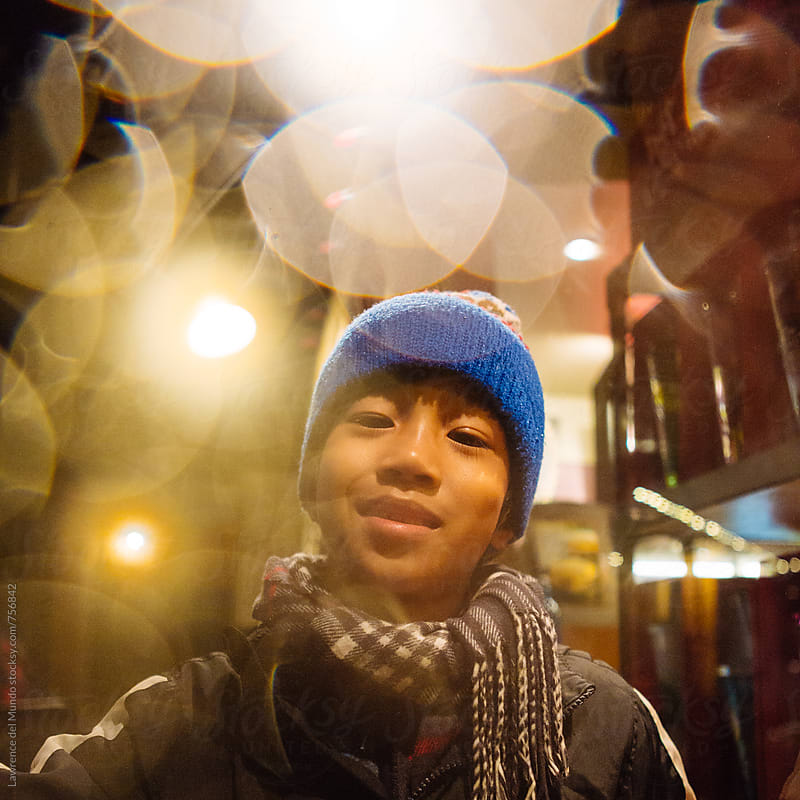 Portrait of a young boy in cold weather clothes looking at the camera by Lawrence del Mundo for Stocksy United