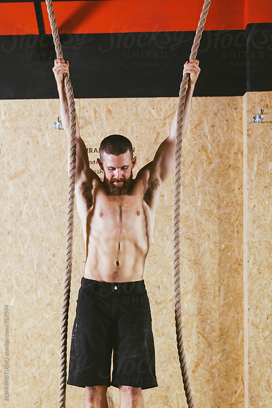 Man with a climbing rope in a gym box. by BONNINSTUDIO for Stocksy United