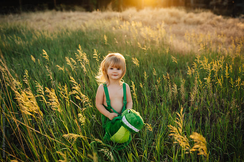 Toddler girl in a dinosaur costume standing in a field at sunset. by Jessica Byrum for Stocksy United