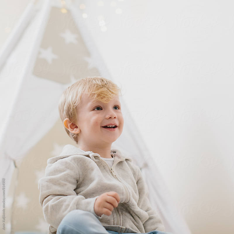 Portrait of cute little boy smiling by Amir Kaljikovic for Stocksy United