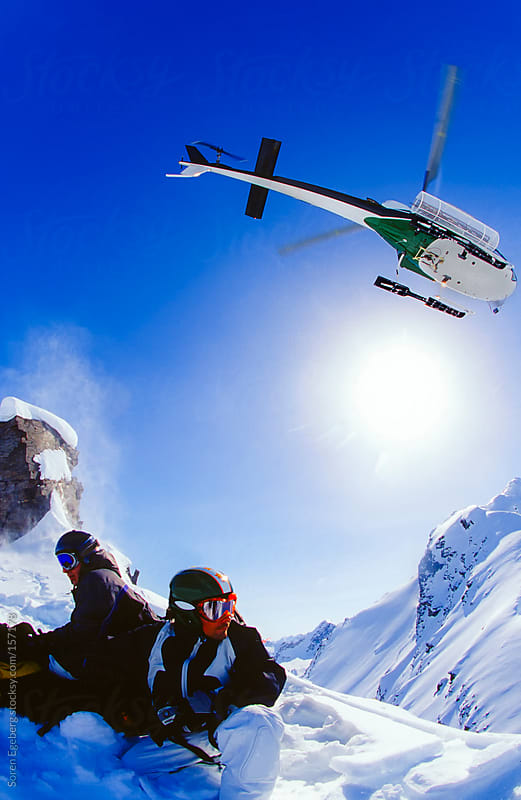 Skier and snowboard sitting in snow looking at helicopter fly away in winter mountains of Alaska by Soren Egeberg for Stocksy United