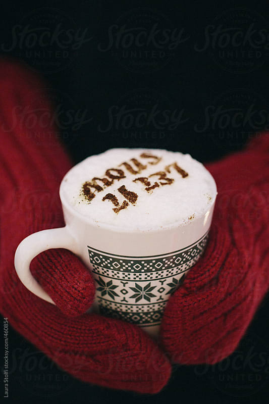 Hands wearing red woolen mittens and holding a mug of chocolate with words Let it snow on foam by Laura Stolfi for Stocksy United