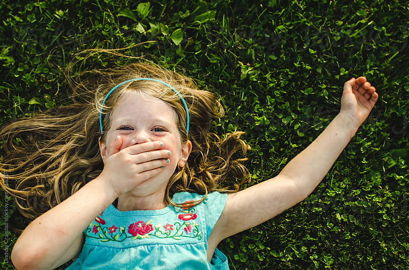 Child laughing while lying in the grass by Lindsay Crandall for Stocksy United