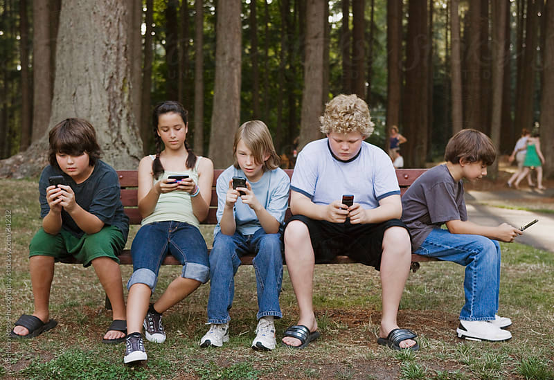 Boys and girls (10-11) using mobile phones in forest by Andersen Ross Photography for Stocksy United