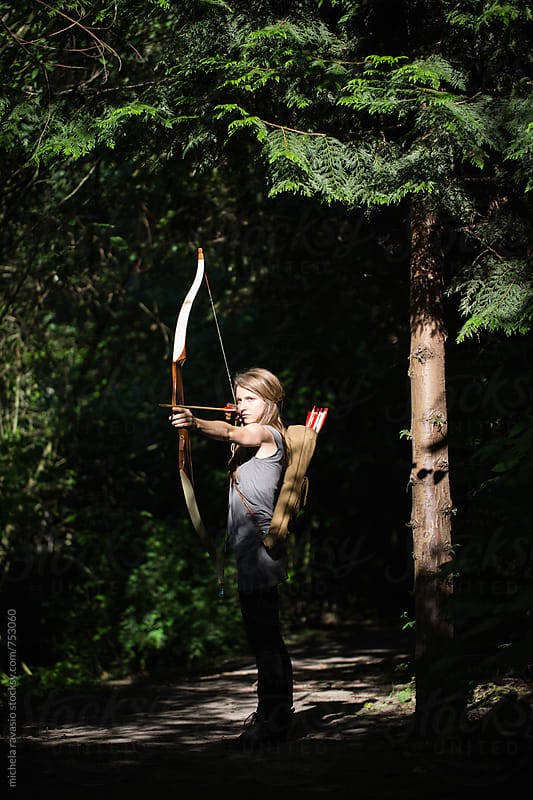 Young woman aiming with archery by michela ravasio for Stocksy United