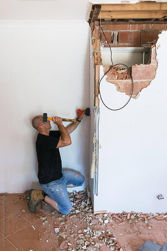 Home Renovator demolishing an internal brick wall by Jacqui Miller for Stocksy United