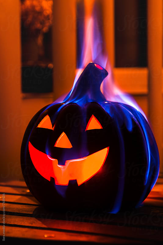 Halloween carved pumpkin burning on the table in a dark room by RG&B Images for Stocksy United