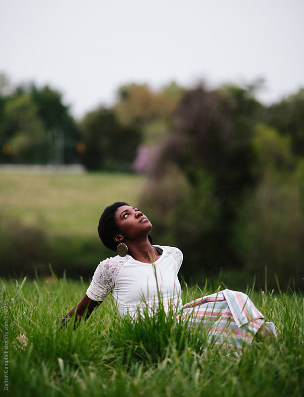 woman siting in grass staring at the sky by Dalton Campbell for Stocksy United