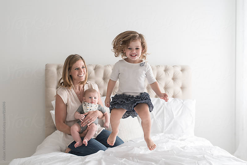 Toddler Jumps On Bed While Mother and Brother Look On by Alison Winterroth for Stocksy United