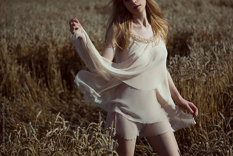 woman in transparent dress outdoor in wheat field by Sonja Lekovic for Stocksy United